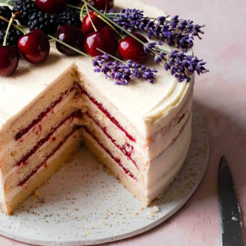 a layered cherry cake with a slice taken out of it