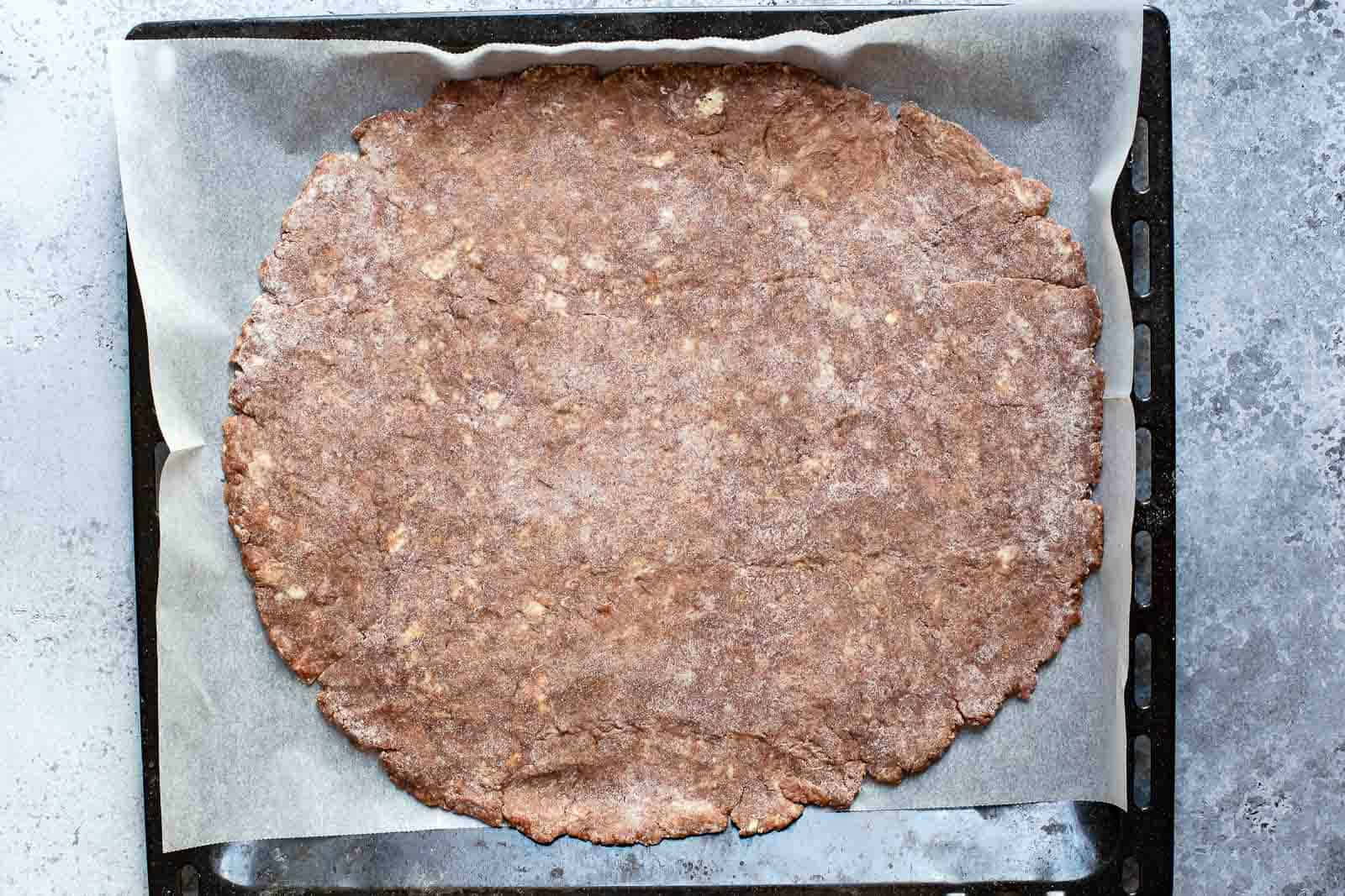 chocolate pie crust flattened out on parchment paper