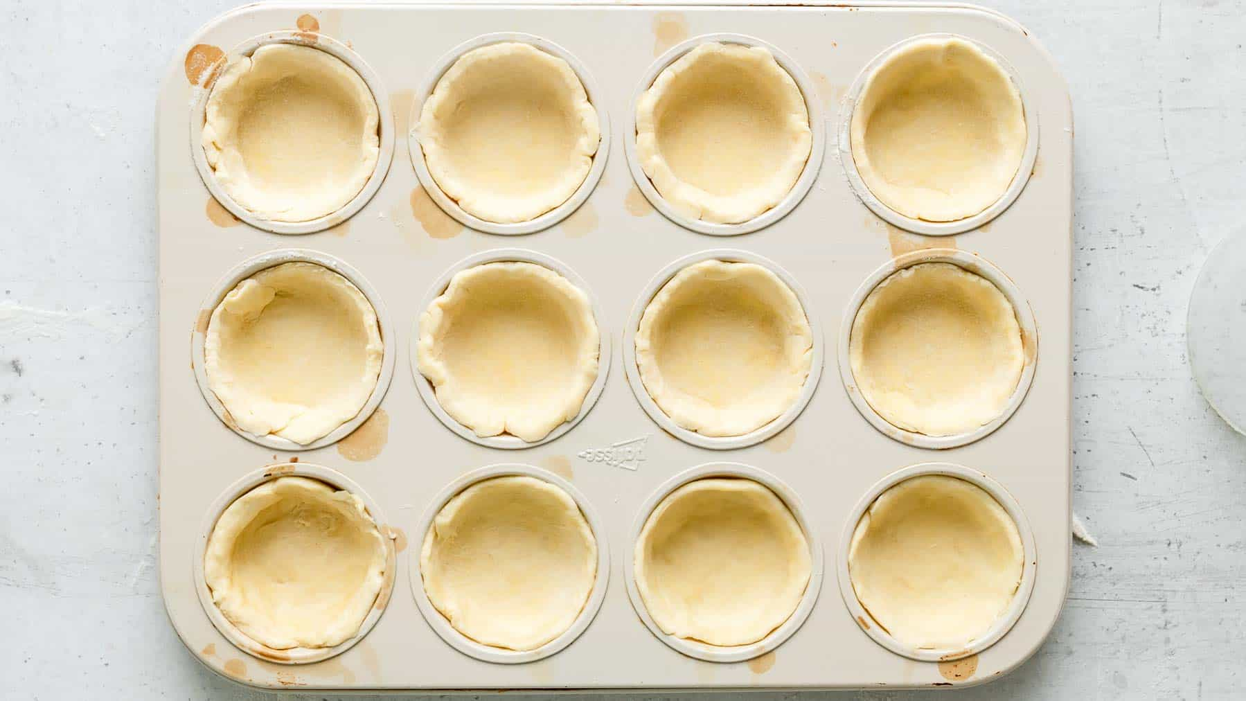 muffin tin with pie crust in each hole
