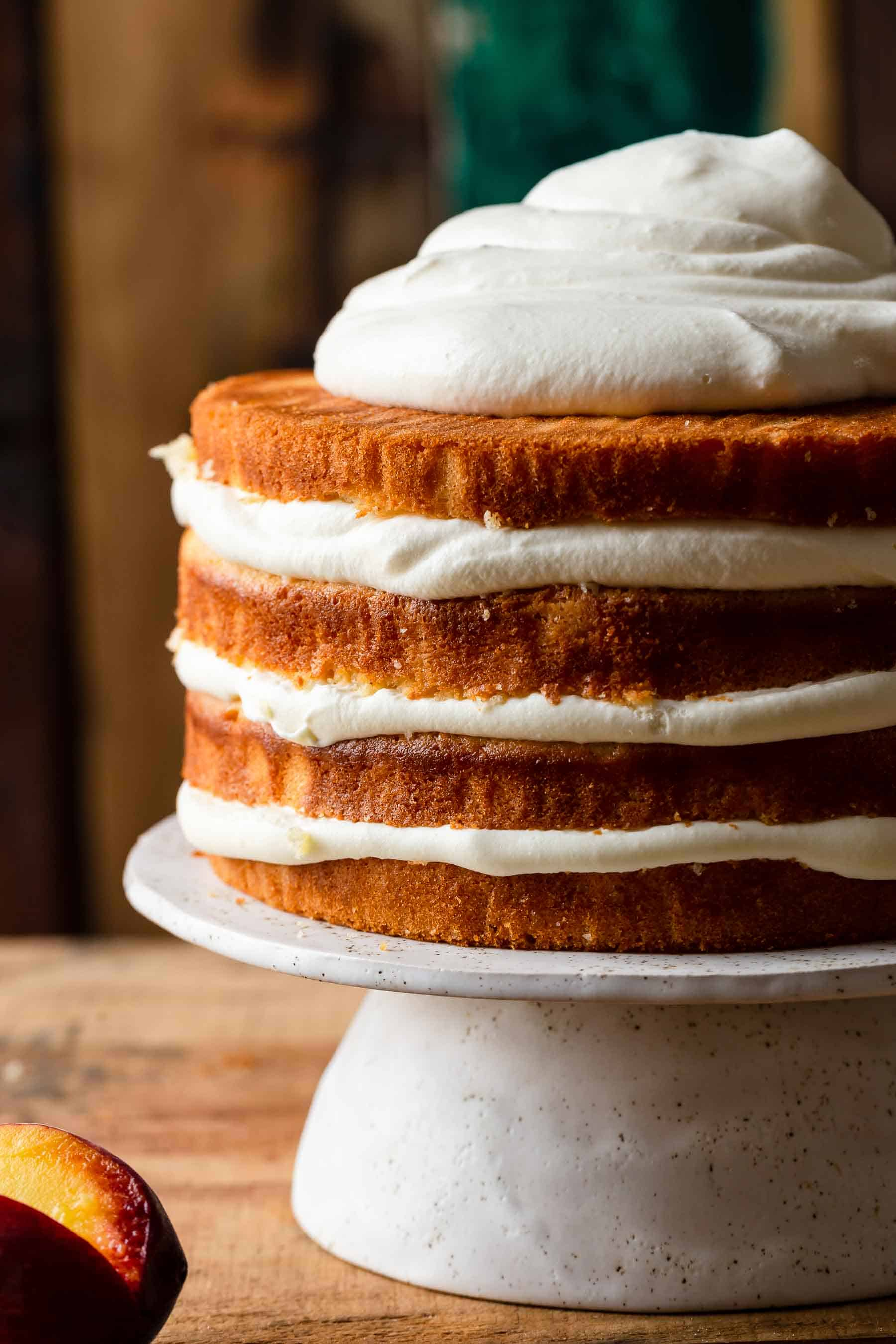 peaches and cream cake on a cake stand