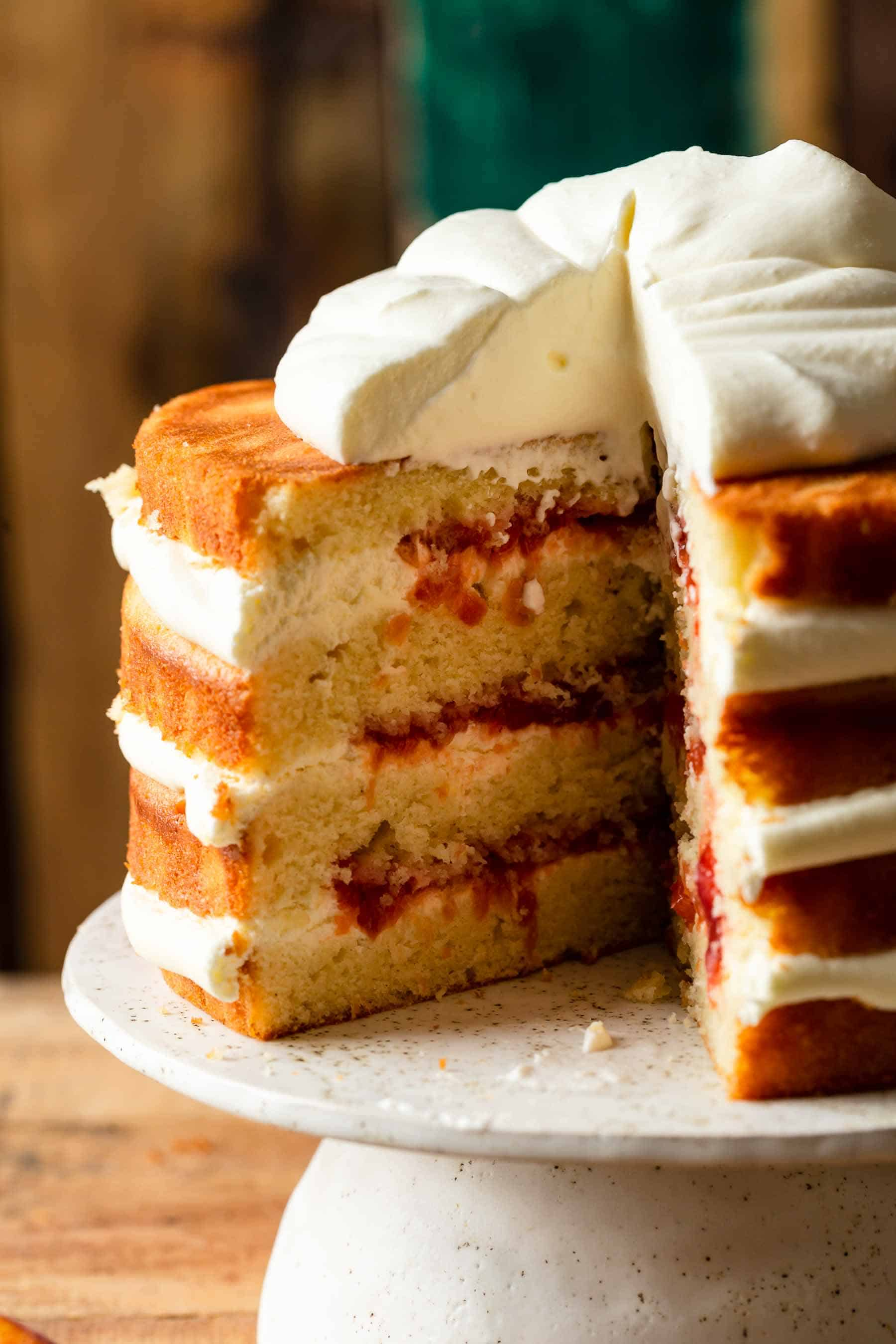 a slice taken out of a layered peaches and cream cake