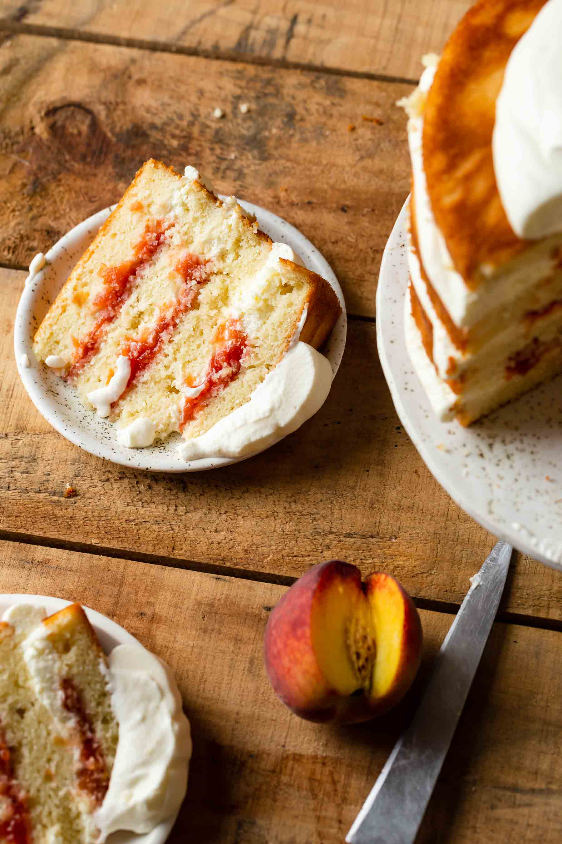 layered peach cake on a table with a peach by it