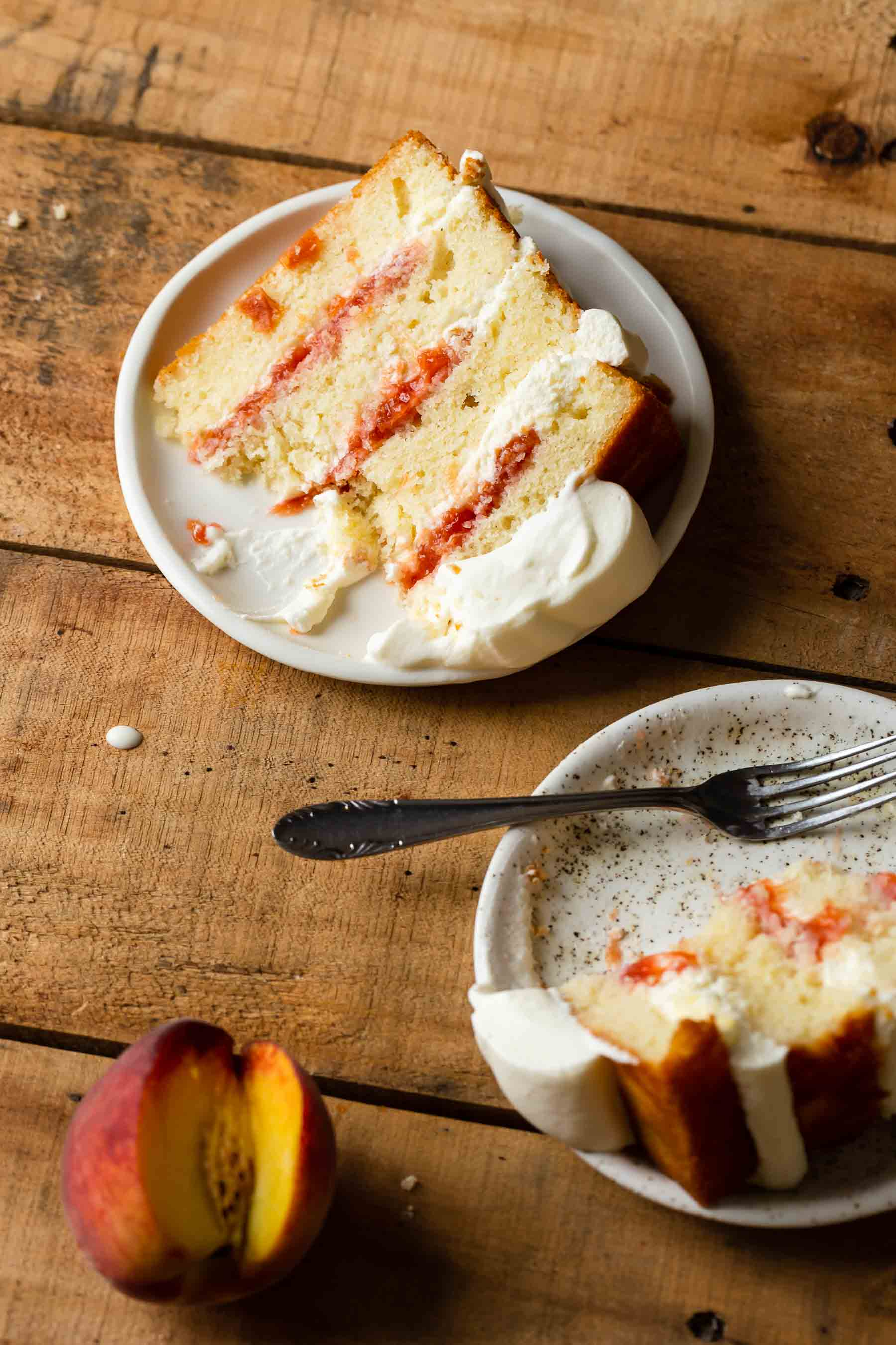sliced peaches and cream cake on a plate with fork