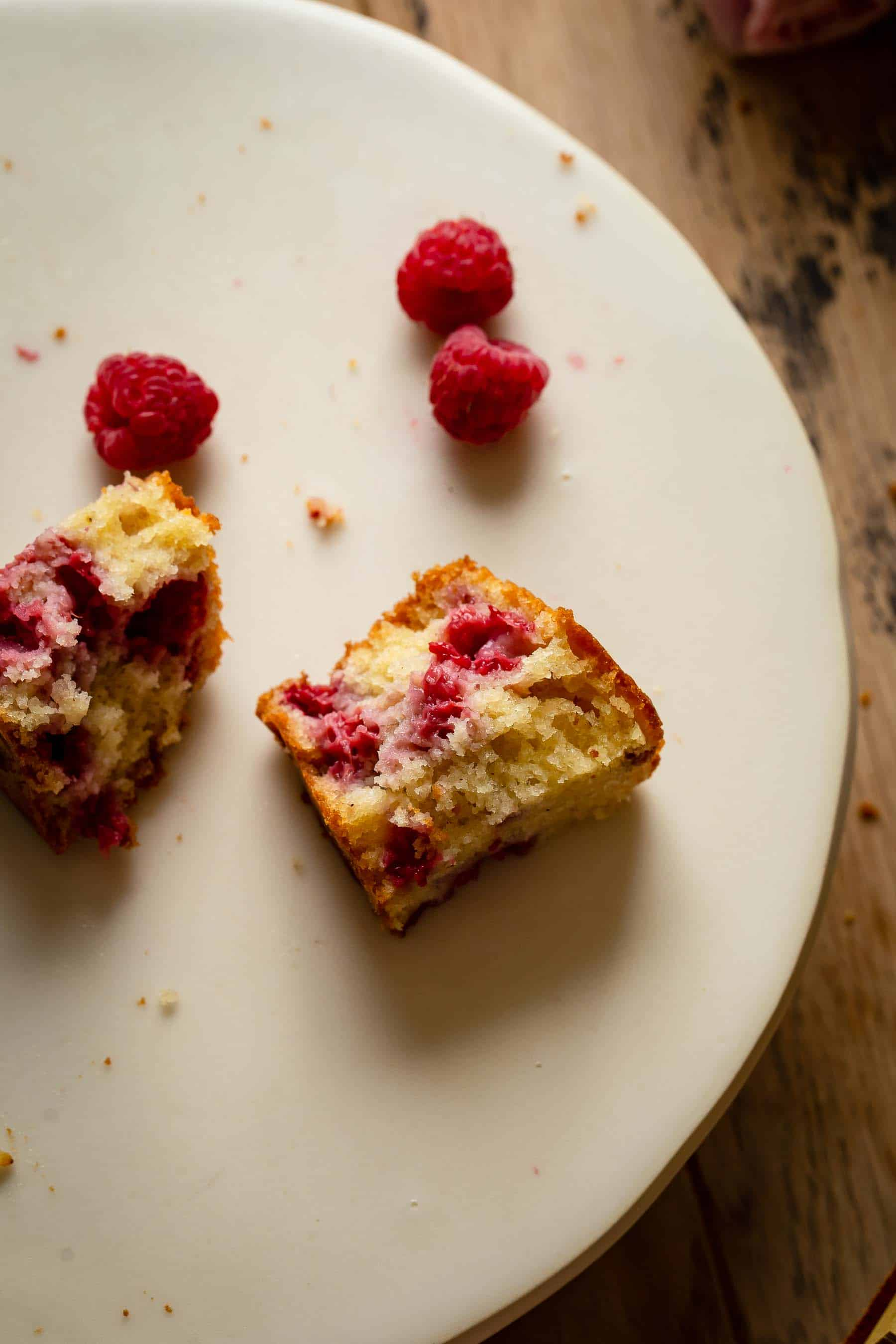 half eaten piece of cake with raspberries by it