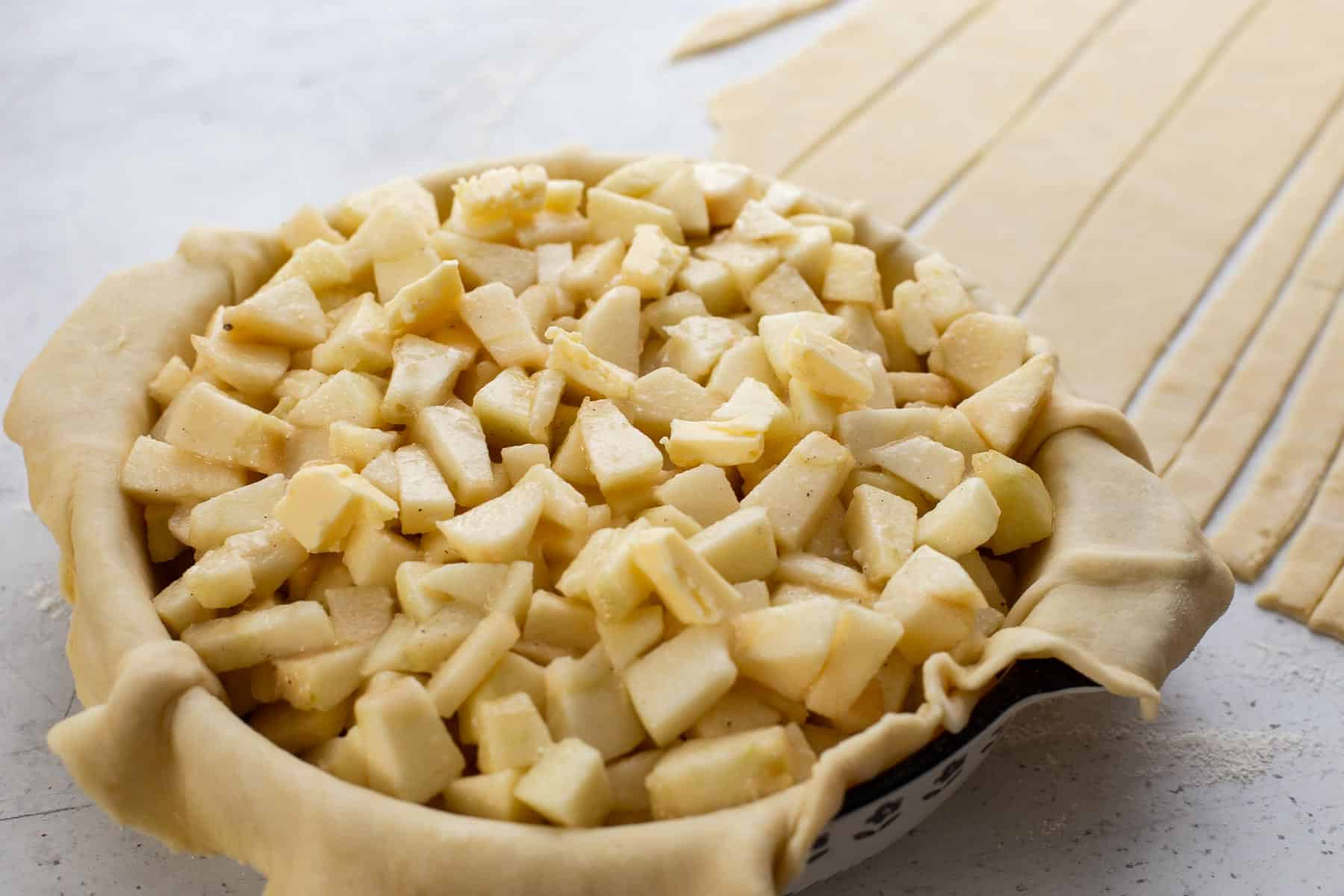 diced up apples in pie crust