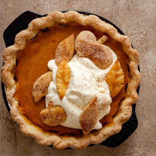baked pumpkin pie topped with whipped cream