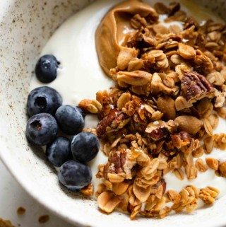 granola in a bowl with milk, peanut butter, and blueberries