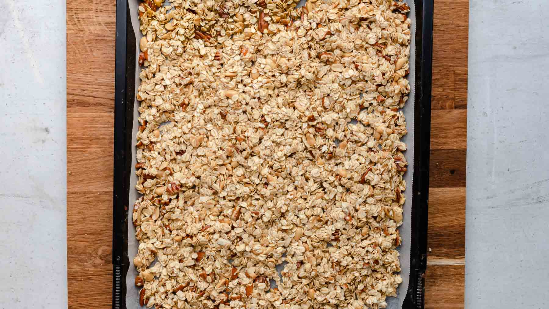 granola layered out on pan ready to be baked
