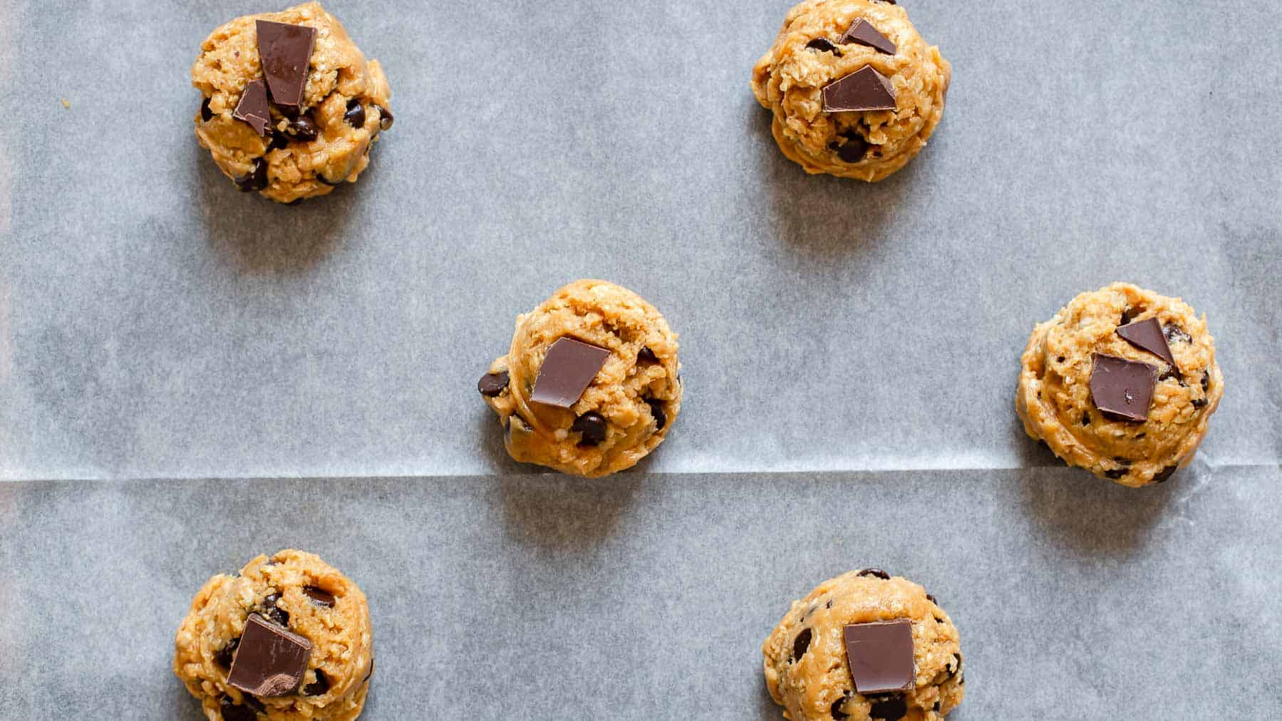scooped cookie dough on baking sheet
