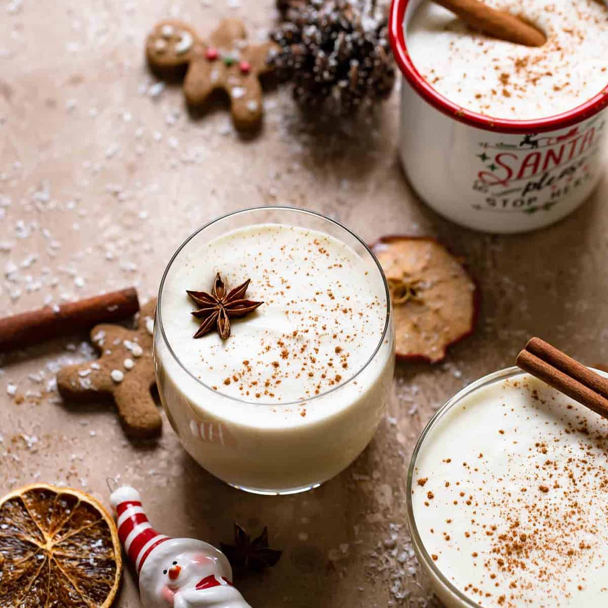 Decorative picture of eggnog in glasses with holiday decoration around on brown background