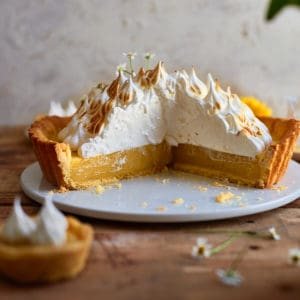 Decorative picture of cut lemon tart on wooden table