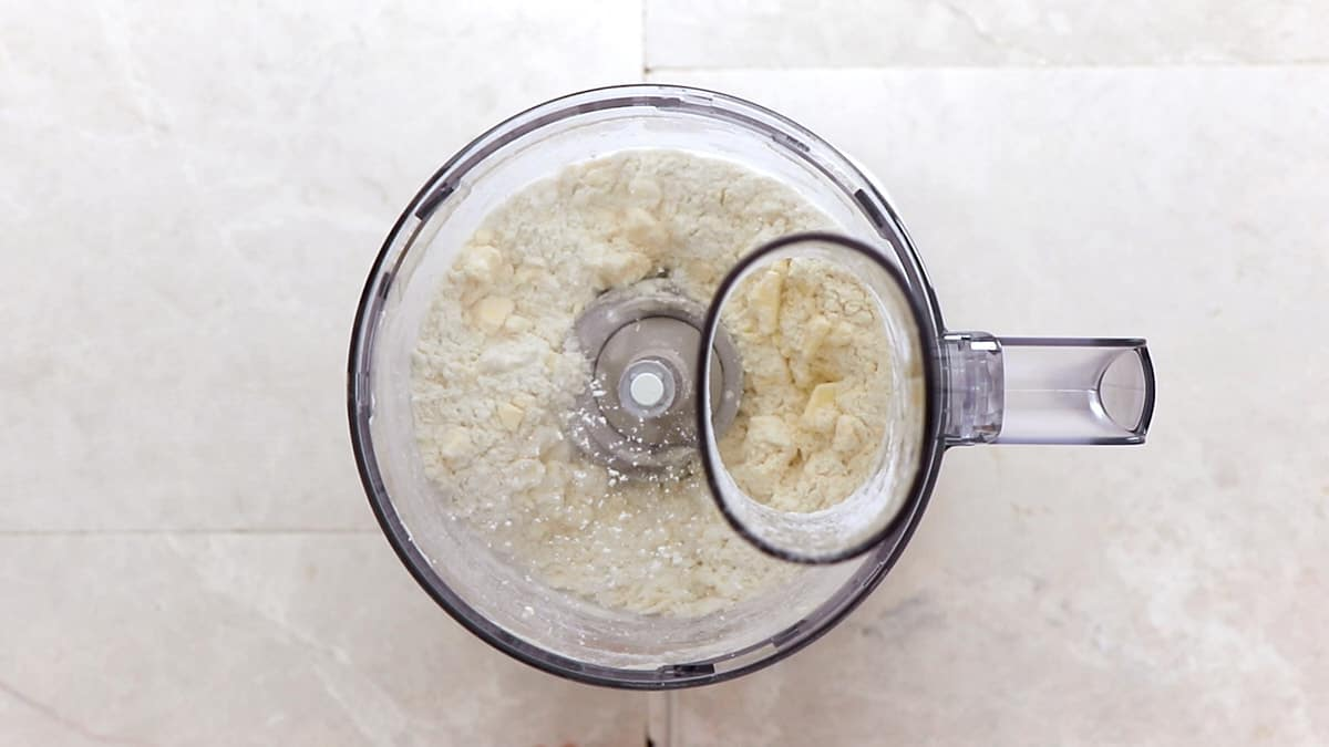 Processed flour, salt, sugar, and butter in a food processor