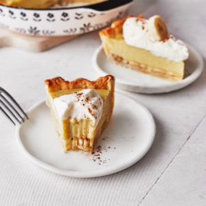 Decorative picture of a bitten banana cream pie slice on a white plate