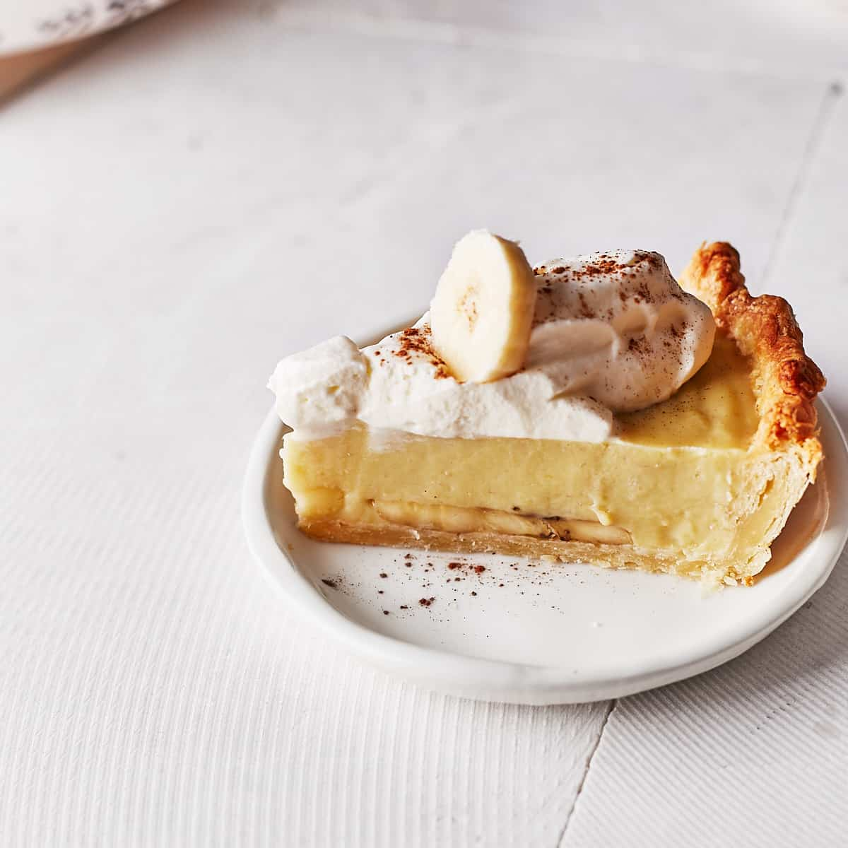 Decorative picture of a cut banana cream pie slice on a white plate