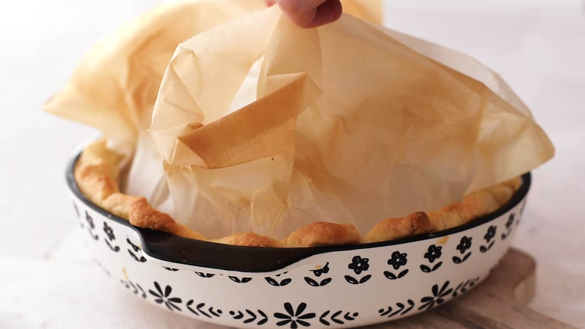 Removing the baking beans from the baked pie crust