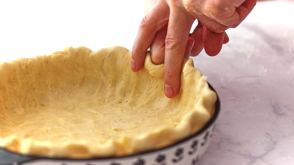 Fluting the edges of the pie crust with knuckles