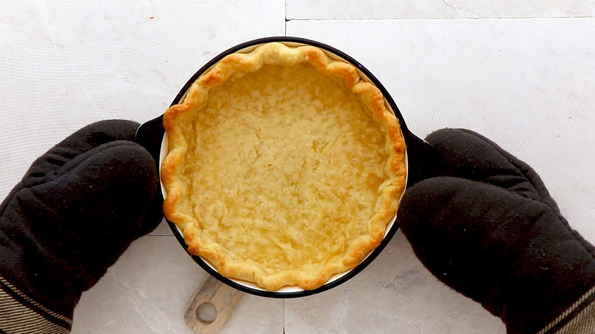 Freshly baked pie crust held up with oven mitts