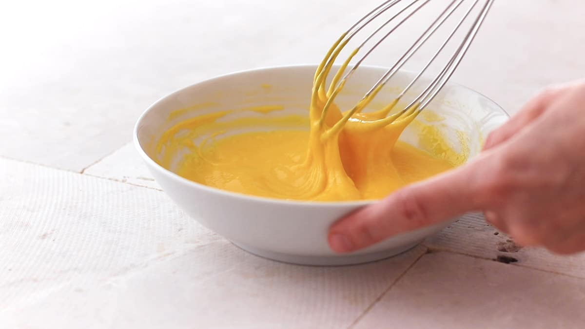 Whisking egg yolks and cornstarch in a white bowl