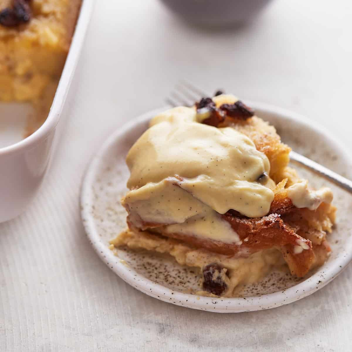 Decorative picture of bread pudding with custard sauce on top on a plate