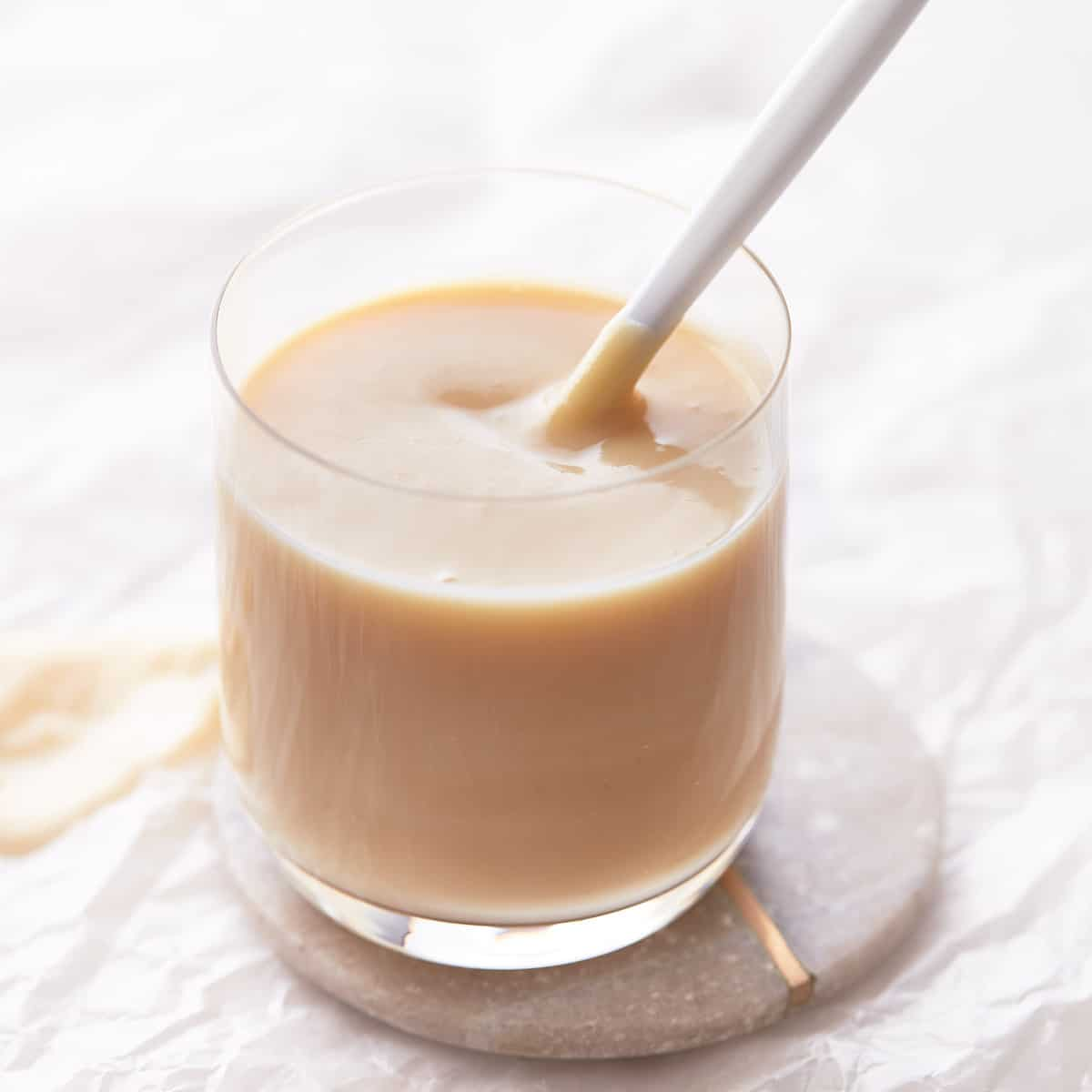 Decorative picture of condensed milk in a glass with a spoon in it
