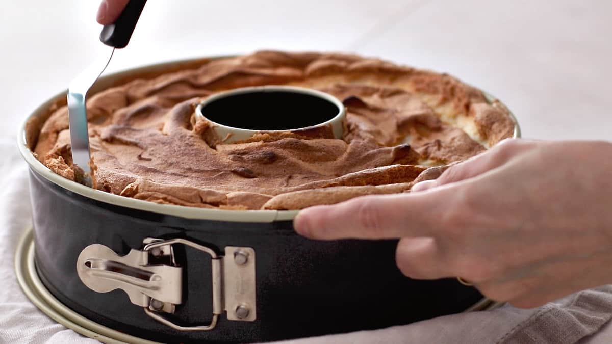 Running an offset spatula around the edges of the pan to loosen the cake