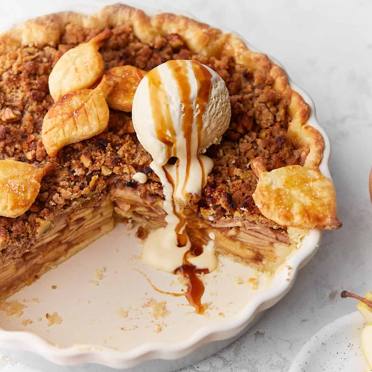 Decorative picture of baked apple crumble pie with ice cream on top on bright background