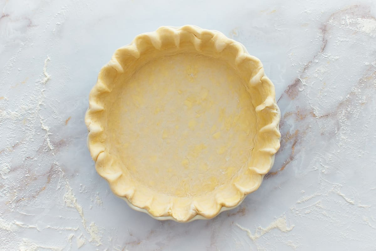 Prepared and fluted pie crust in baking dish