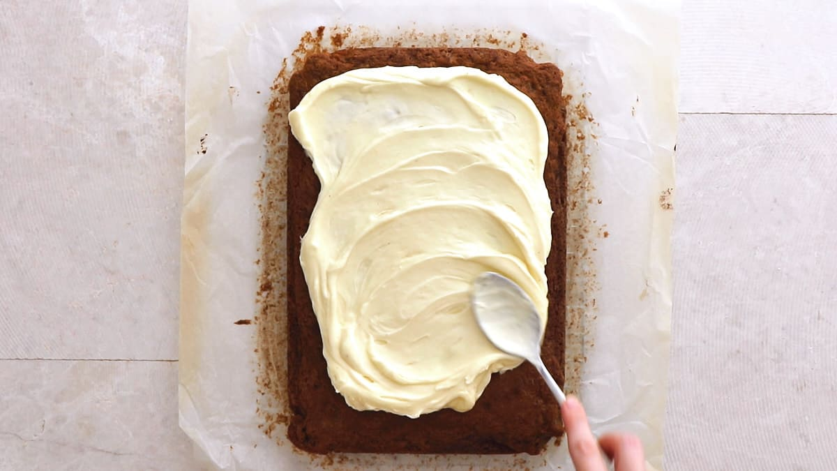 Spreading frosting on top of the baked cake with the back of a spoon