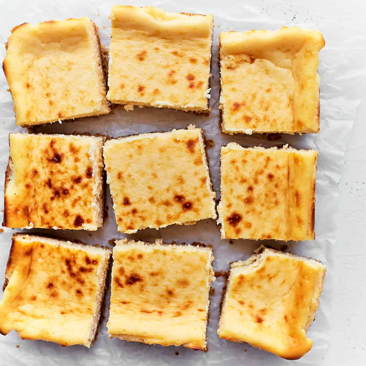 Decorative picture of cut cheesecake bars on white background