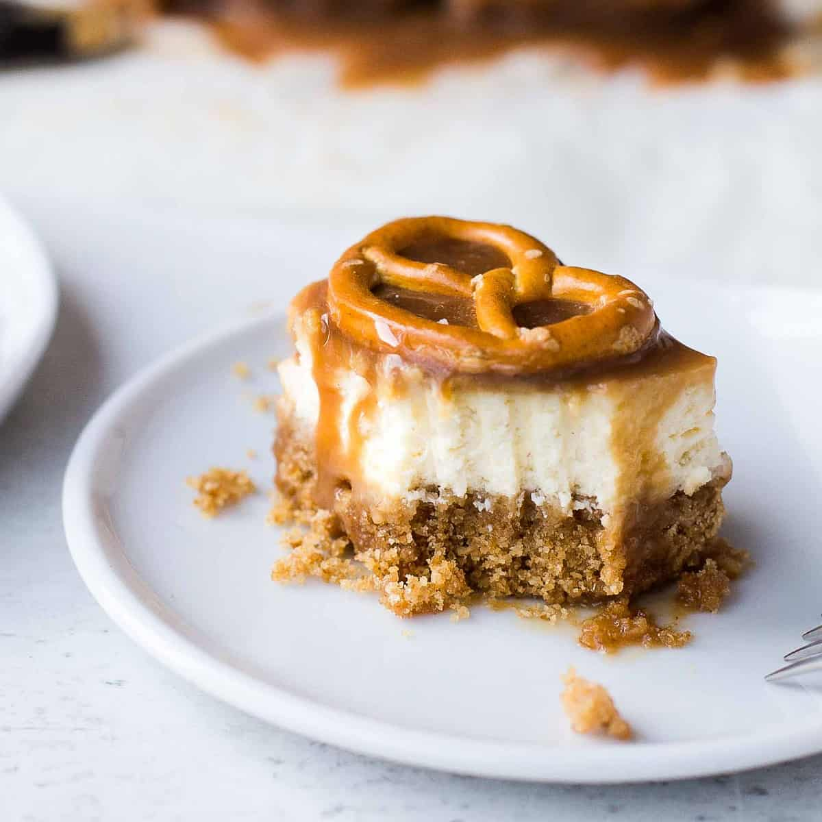 Decorative picture of cheesecake bars topped with caramel and pretzels