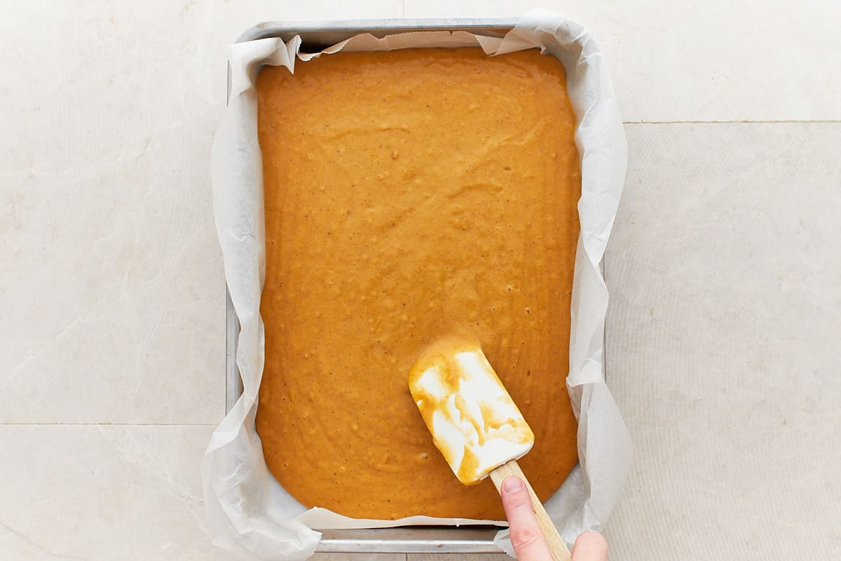 Spreading cake batter in a paper-lined baking pan