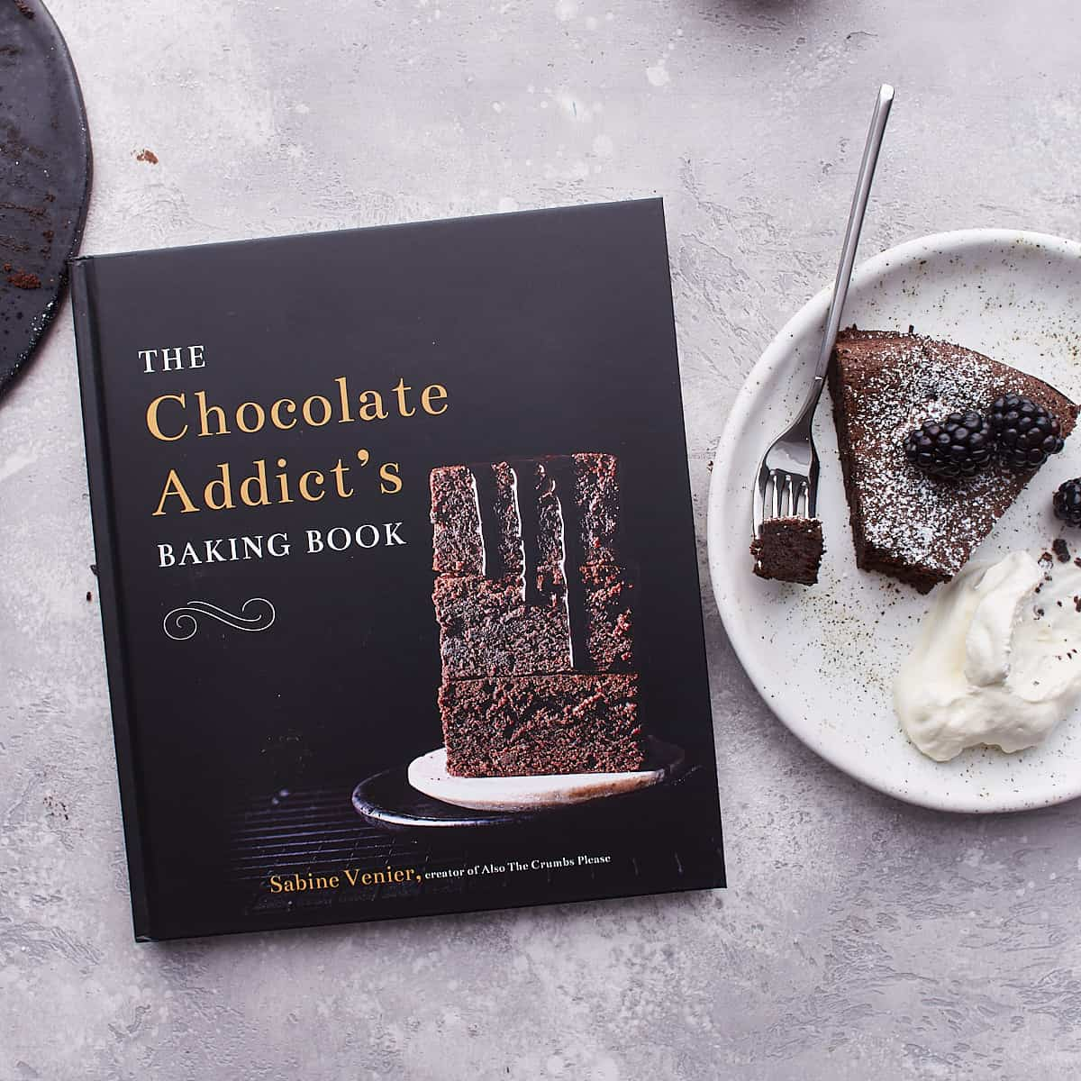 Photo of a chocolate cookbook with a plated slice of cake next to it
