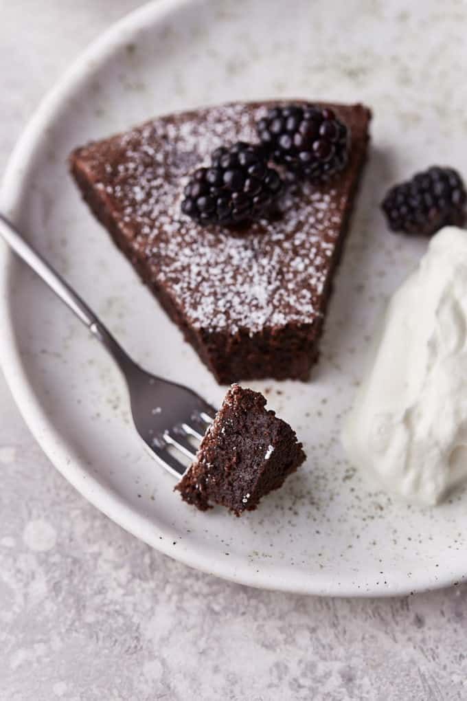 Sugar dusted chocolate cake on a dessert plate with berries on top and whipping cream