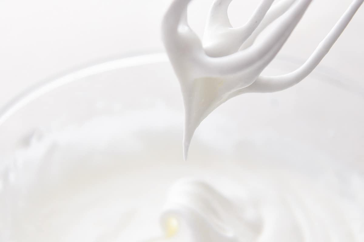 Whipped, glossy, stiff egg whites mixture on a whisk attachment