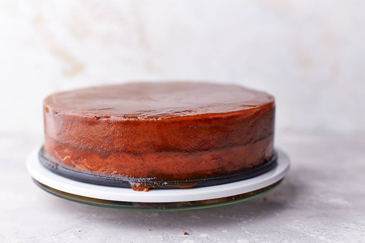 Chocolate cake glazed with jam on a serving plate