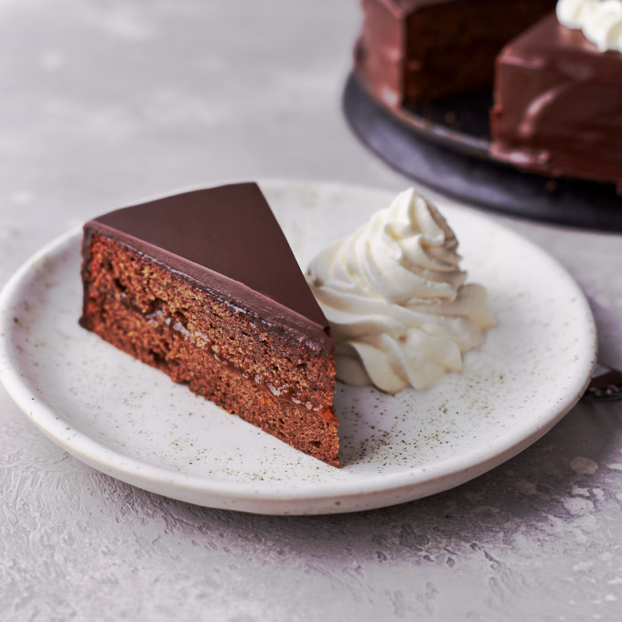 A slice of sacher torte with whipped cream on a dessert plate