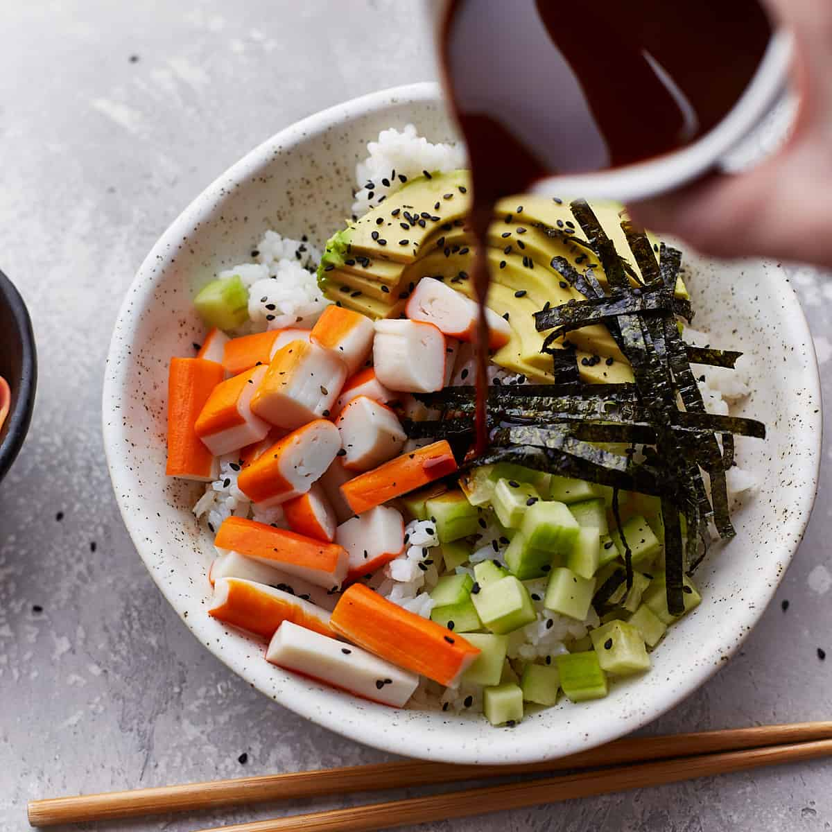 Pouring sushi sauce over a sushi bowl