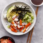 Raw ingredients and vegetables arranged on top of cooked rice in a bowl