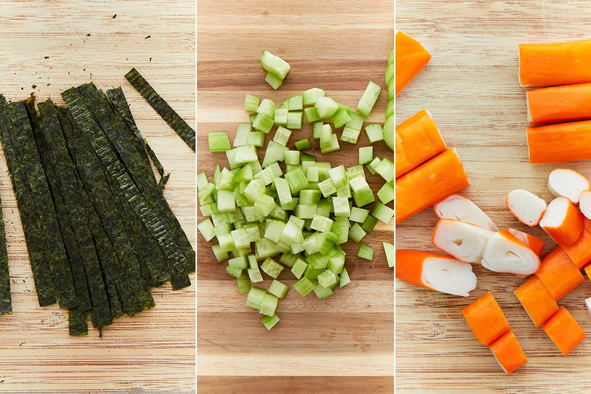 Cut nori sheets, cucumber, and imitation crab meat on wooden boards