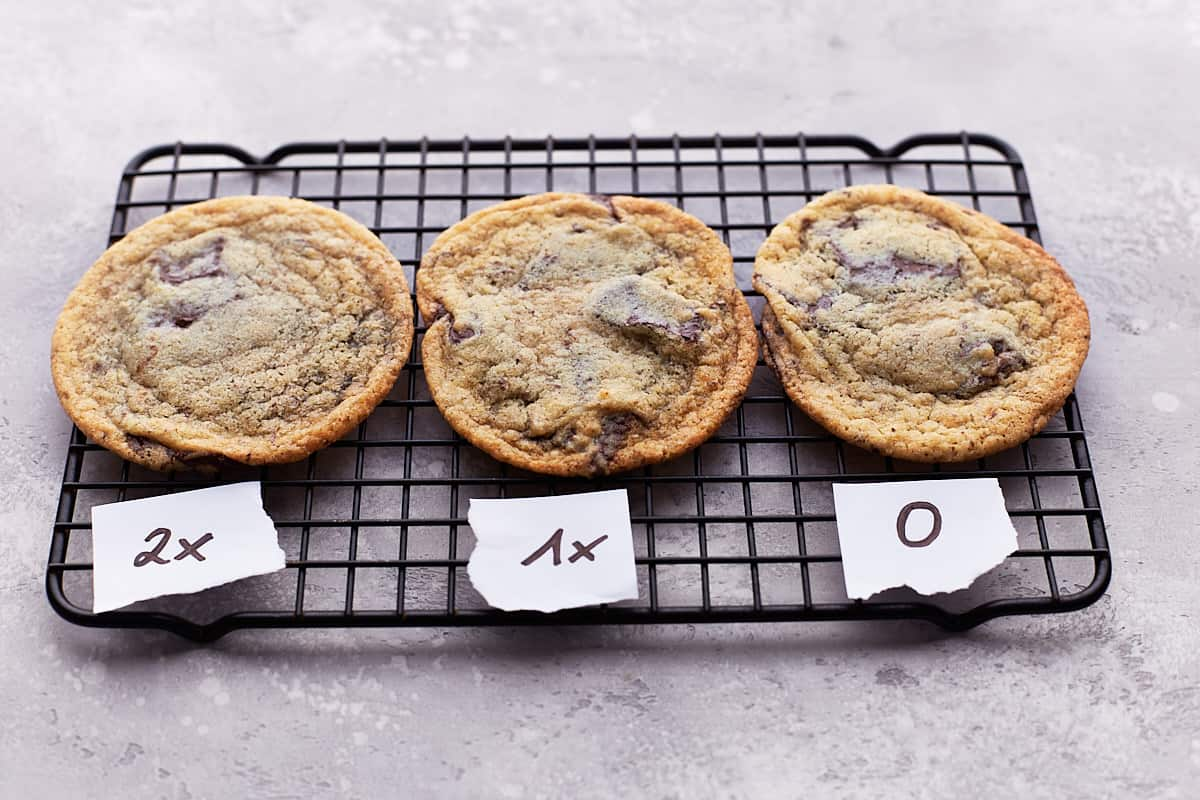 Three differently baked cookies on cooling rack shown from the side with labels 2x, 1x, 0