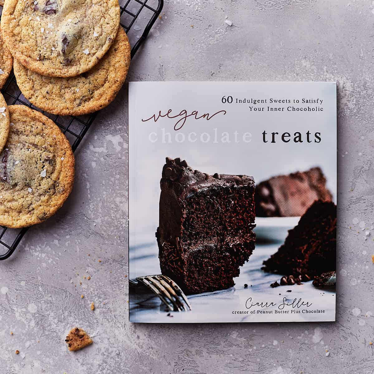 "Photo of a cookbook ""vegan chocolate treats"" next to a stack of cookies"
