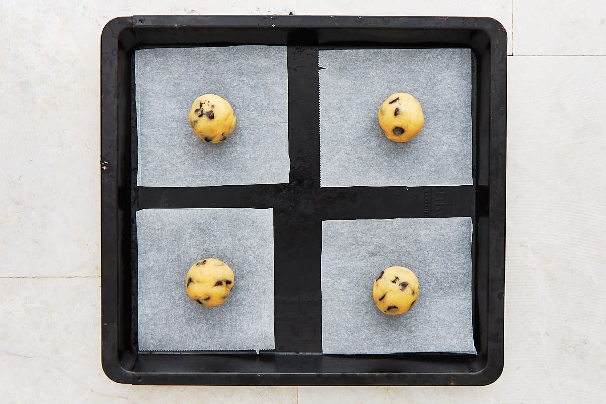 Four balls of cookie dough on single cut baking paper pieces on a baking sheet