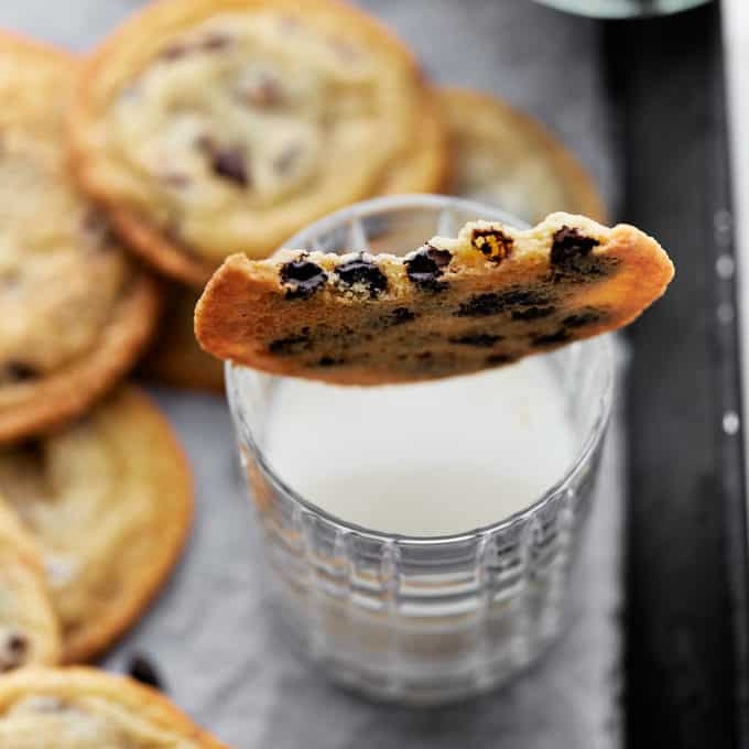 Bitten cookie placed on top of a glass of milk surrounded by other cookies