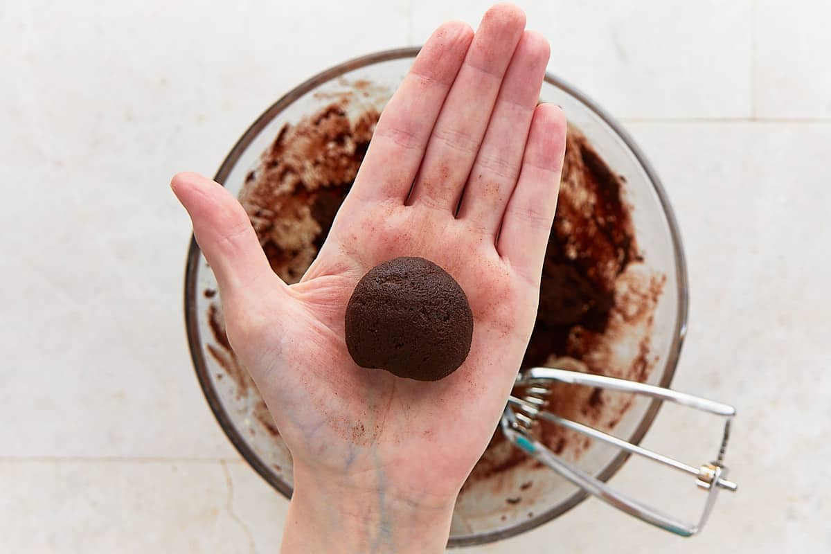 Holding a rolled ball of cookie dough in the hand