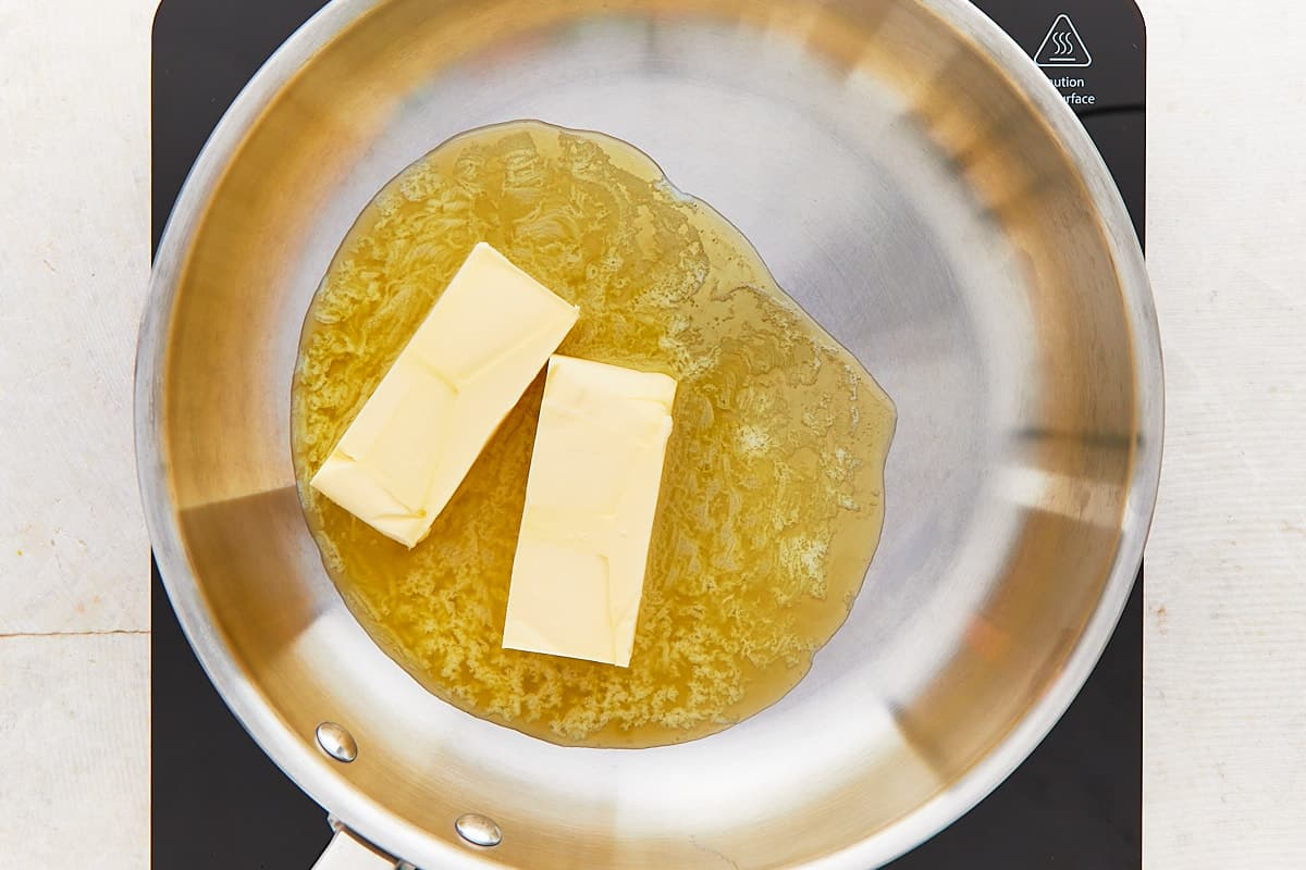 Two sticks of butter melting in a light-colored pan