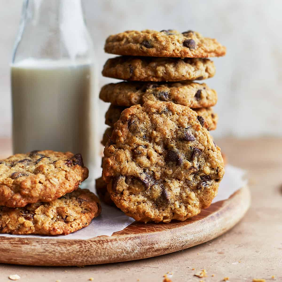 Stack of oatmeal cookies next to glass of milk