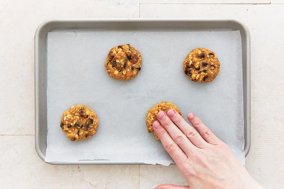Flattening balls of cookie dough on a baking sheet
