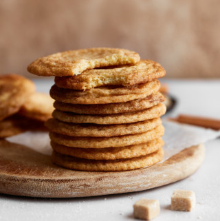 A stack of cookies on a wooden board with sugar and cinnamon decoration around it