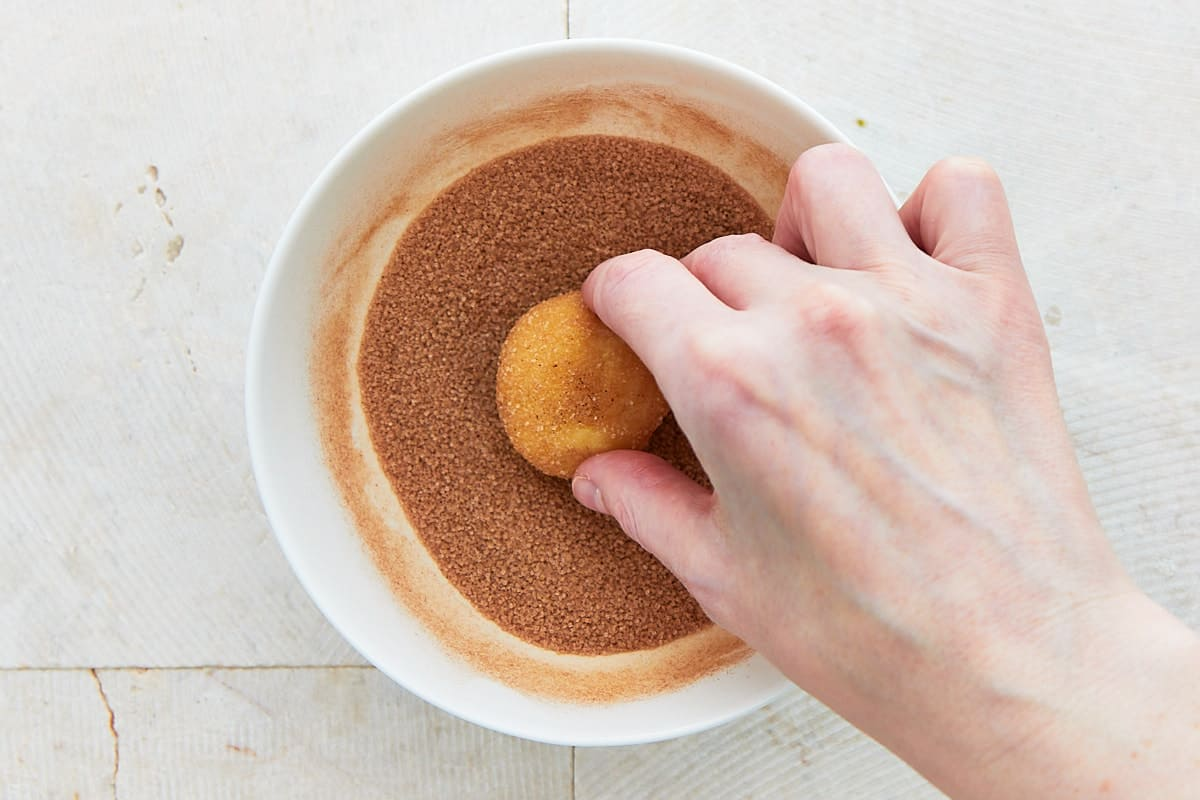 Rolling a ball of cookie dough in a bowl half full with sugar and cinnamon