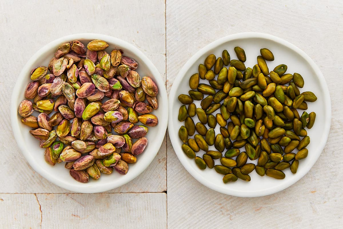 Two different types of pistachios on two white plates